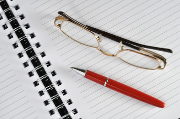 eye glases and red pen on the notebook