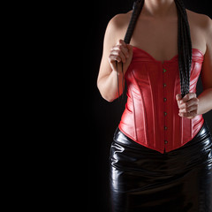 Woman in red leather corset with black whip