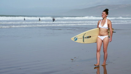 Woman with surfing board on the beach