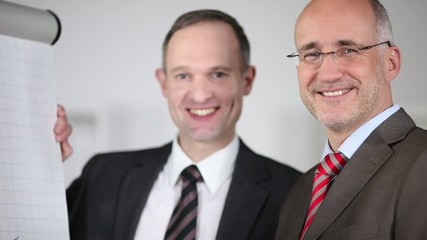 zwei lächelnde geschäftsmänner stehen am flipchart