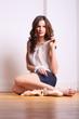 tänzerin sitzt auf holzboden mit ballettschuhen