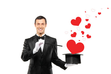 Smiling magician and a red heart shaped objects coming out of a