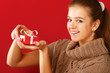 Young woman holding gift box isolated on red background