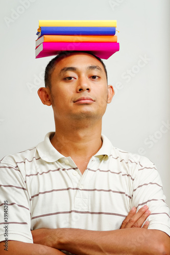 confident asian student with books on head