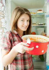 girl eating  soup from pan near fridge