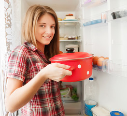 girl putting pan into refrigerator