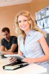 Beautiful office worker using tablet in office