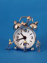 Eine Uhr umgeben von vielen kleinen Arbeitermaennchen....