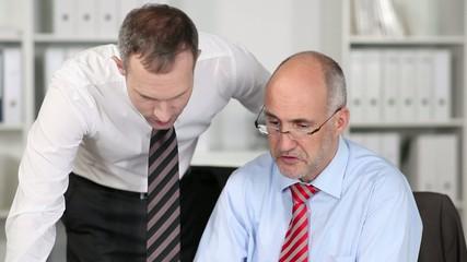 chef erklärt einem mitarbeiter etwas am laptop