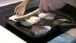Mujer cocinando pescado blanco a la plancha