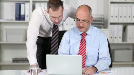 zwei kollegen in einer besprechung am notebook