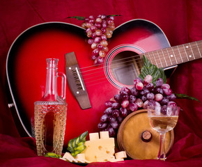 wine, grape and guitar on red background