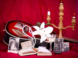 candlestick, guitar, lily, old photos, book on red background