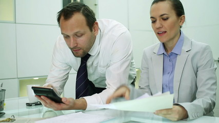 Business couple making calculations using a calculator