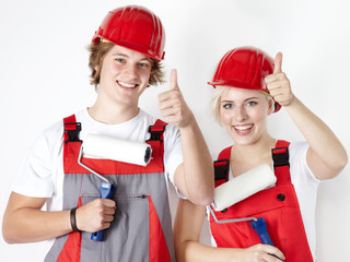 Two worker showing thumps up after painting a wall
