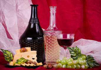 with wine, grape and cheese on red background