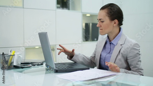 Frustrated businesswoman with laptop in the office, slow motion