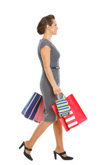 Woman in dress walking with shopping bags