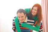 Smiling redhead girl piggybacking boyfriend