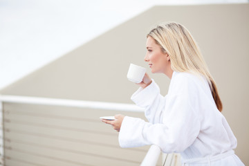 young woman in bathrobe drinking coffee on balcony