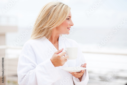 beautiful young woman in bathrobe drinking coffee in the morning