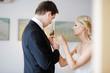 Beautiful bride adjusting groom's boutonniere