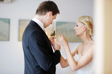 Beautiful bride adjusting groom's boutonniere