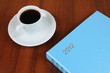 Cup of coffee and notebook on table