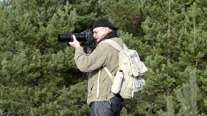 Photographer in coniferous forest