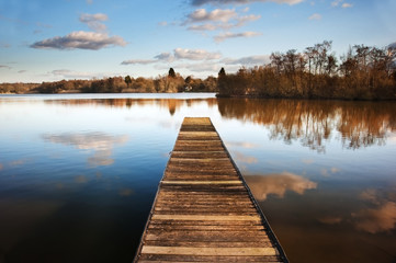 Landscape of fishing jetty on calm lake at sunset with reflectio