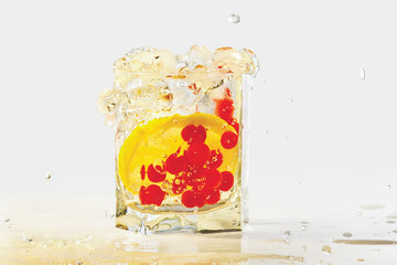 Glass of water, ice, lemon and red cranberries with splash
