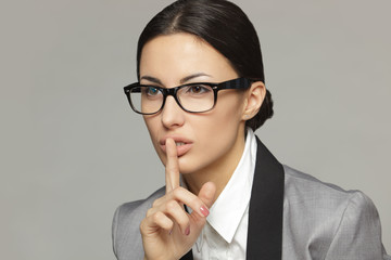Closeup of businesswoman with finger on lips