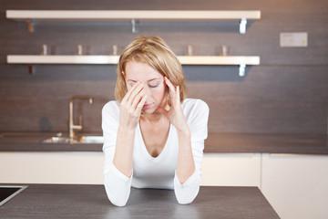 junge Frau mit Kopfschmerzen in der Küche