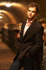 blond young man in a wine cellar,holds a wine glass in his hands