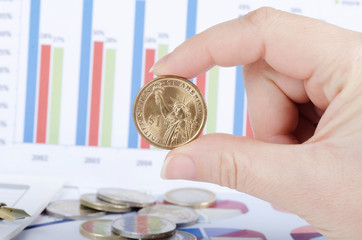 Coins in a hand against business of diagrammes