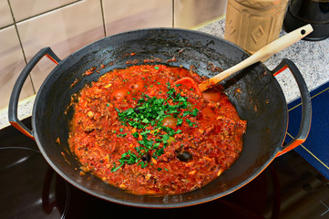Bolognese sauce cooking in a wok on an induction cooker