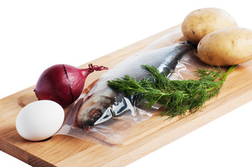 Vegetables and a salty herring on a kitchen board