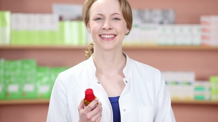 lächelnde verkäuferin mit medikament in der apotheke