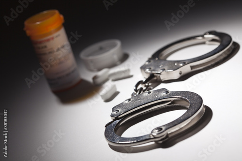 Handcuffs, Medicine Bottle and Pills Under Spot Light