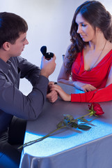 The guy gives the girl a ring