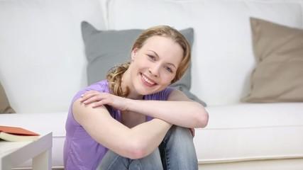 blonde frau sitzt entspannt im wohnzimmer