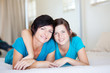 middle aged mother and teen daughter lying on bed relaxing