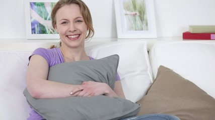 lachende frau zuhause auf dem sofa