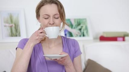 frau genießt ihren kaffee auf dem sofa