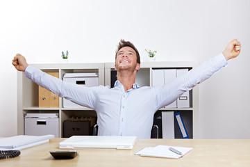 Mann im Büro jubelt am Schreibtisch