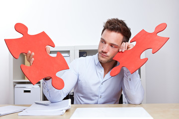 Nachdenklicher Mann im Büro mit Puzzleteil