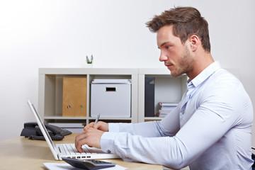 Mann am Laptop beim Onlinestudium