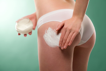 Woman apply cellulite cream on bottom