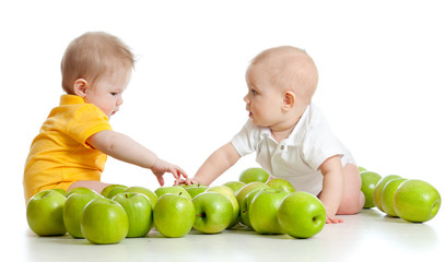 Two little children with green apples isolated on white backgrou
