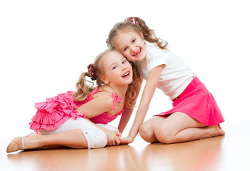 Two girls are playing together. Isolated over  white background